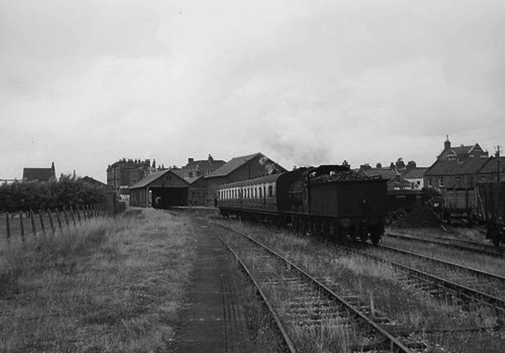 Train leaving the short original platform. On the right can be seen the part of the coal yard with coal trucks.